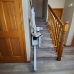 Handicare 1100 stair lift folded up at bottom of stairs