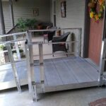 Wheelchair ramp leading to front door of home with side entrance