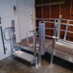 Wheelchair ramp leading to garage entry door with steps