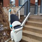 Handicare 1000 outdoor stair lift folded up at bottom of porch steps