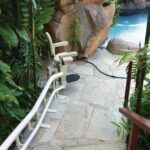 Harmar Helix outdoor curved stair lift on stairs leading to pool